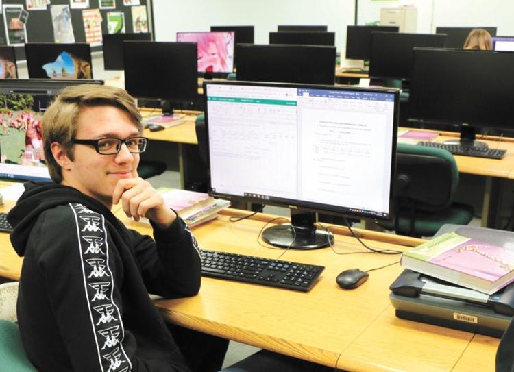 Hayward student sits next to computer.